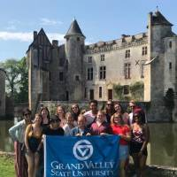 GVSU Students in front of a castle in France holding a GVSU flag